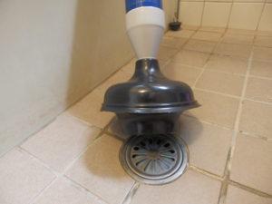 真空式パイプクリーナーをお風呂の排水口に押し当てる